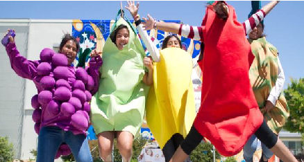 Photo of people wearing fruit and veggie customes jumping excitedly.